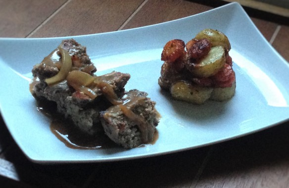 Meatloaf served with roasted baby potatoes and carrots and onion gravy.